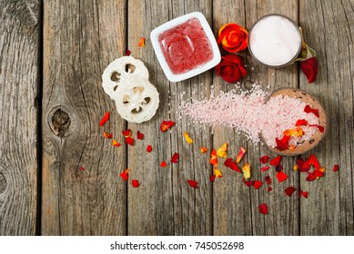 facial mask and moisturizer with roses on weathered wooden