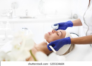 Facial mask . The woman in the beauty salon, beautician applied with a brush to the face mask.