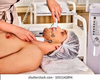 Facial massage at beauty salon. Electric stimulation skin care of man. Equipment for microcurrent lift face. Anti aging face and neck and close up rejuvenation. Acne Removal.