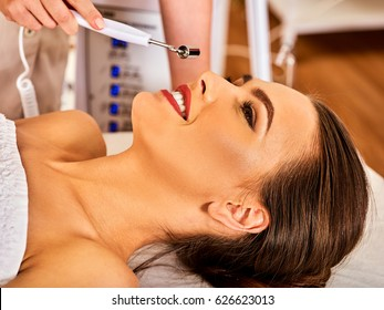 Facial massage at beauty salon. Electric stimulation skin care of woman. Professional equipment for microcurrent lift face. Anti aging neck non surgical treatment. Electrical appliance close-up.