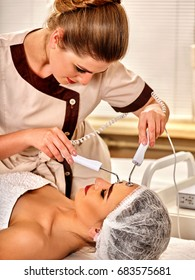 Facial massage at beauty salon. Electric stimulation skin care of woman. Professional equipment for microcurrent lift face. Anti aging rejuvenation and non surgical treatment number one.