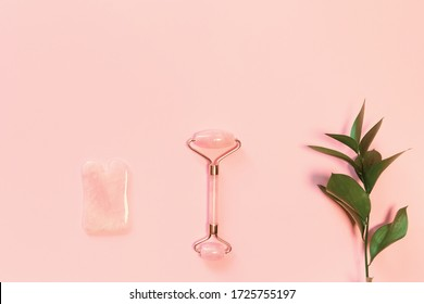 Facial massage kit. Face roller and gua sha massager made from natural stones on pastel pink background. Skin care concept