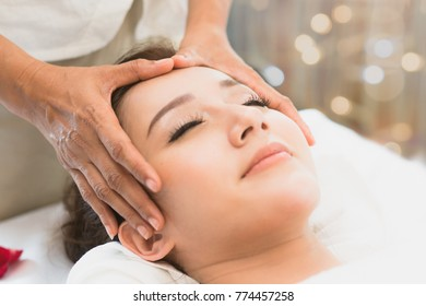 Facial massage in spa salon. Relaxation Beautiful woman lying on the bed and doing facial treatment in spa salon by masseur. Selective focus on thumb of masseur.
