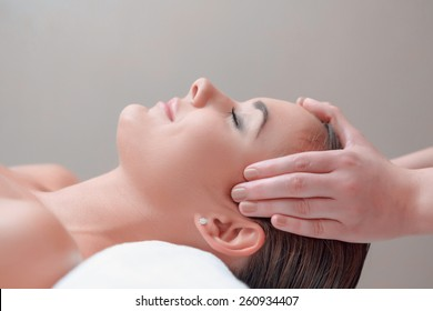 Facial massage. Top view of attractive young woman lying on back and keeping her eyes closed while massage therapist massaging her face