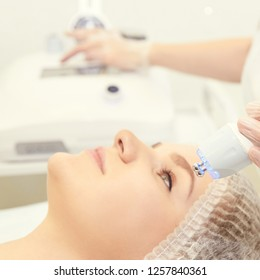 Facial micro current cosmetology procedure. Beauty technology treatment. Woman face therapy.