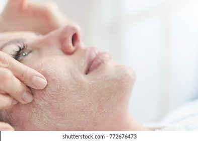 Facial peels in the beauty spa salon. Mask with scrub for rejuvenation skin face. Happy and relaxed middle aged woman. Face massage