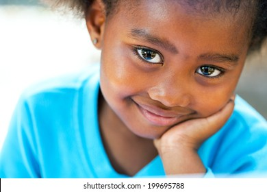 Facial portrait of cute African girl resting cheek on hand.