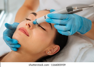 Facial procedure. Delighted nice woman lying on the medical bed with her eyes closed while having hydrafacial