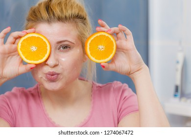 Facial skin and body care, vitamins good complexion treatment at home concept. Young woman having gel mask on her face holding orange fruit.