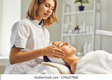 Facial skin care procedures. Beautician makes a massage procedure with a woman's face in a cosmetic clinic