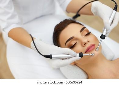 Facial Skin. Closeup Of Beautiful Woman Receiving Facial Microcurrent Treatment From Therapist At Spa Salon. Beautician Using Electrical Impulses For Facial Procedures. Cosmetology. High Resolution