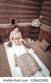 Facial therapy. Top view of a skilled Asian woman doing facial massage for her client