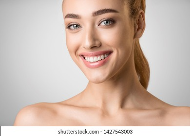 Facial Treatment. Beautiful Woman with Clean Fresh Skin Over Grey Background