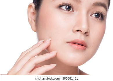 Facial treatment. Beautiful Young Asian Woman with Clean Fresh Skin touch her face .