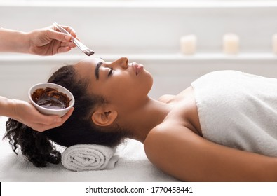 Facial treatment concept. Side view of african woman getting facial mask at spa