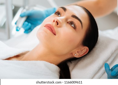 Facial treatment. Nice young woman lying on the medical bed while having a beauty procedure