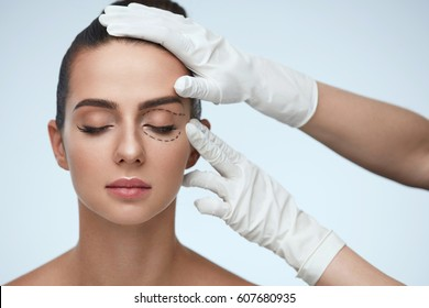 Facial Treatment. Portrait Of Beautiful Sexy Woman With Closed Eyes And Black Surgical Lines On Skin. Closeup Of Hands Touching Young Female Face. Plastic Surgery Concept. High Resolution