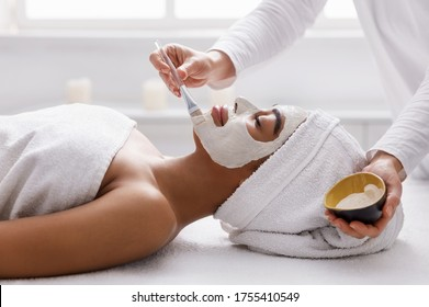 Facial treatment. Therapist applying clay face mask on black girl, spa interior