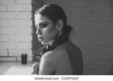 facial treatment. Woman with braid hair at window. Girl with makeup face on white brick wall. Beauty, hairdressing salon. Hairstyle, cosmetics, visage. Loneliness, solitude, depression concept