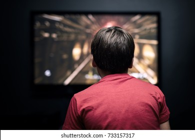 Facing back caucasian little boy watching television. Television and video game addiction.