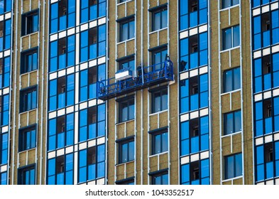 Facing the building with a ventilated facade. Aluminum colored facades. Modern facades of high-rise buildings. Construction of a large residential complex. Suspended construction cradle.