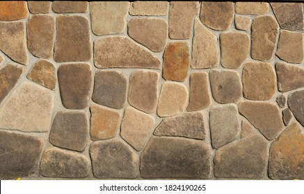Facing stone brick wall texture background. Modern slate outdoor decorative rocks. Aged grungy coarse stonework city. Tile textured of general layout of stones masonry with mixed block various shapes.