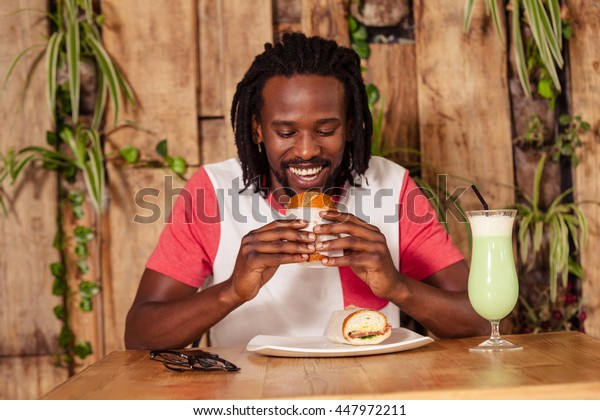 Facing view of hipster man eating sandwich at cafe