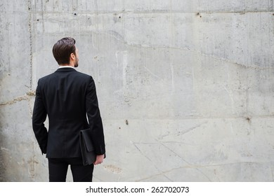 Facing a wall. Rear view of young man holding briefcase while standing outdoors and against the concrete wall