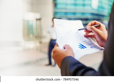 Fact sheet of a mutual fund with graphs in a hand of businessman