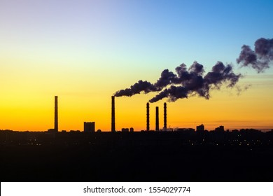 factories smoke from pipes at sunset
