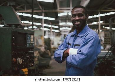 Factory african american worker or technician looking at camera and cross his arms with confident action.Industrial engineer at manufacturing plant.