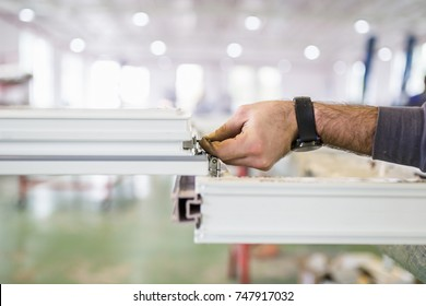 Factory for aluminum and PVC windows and doors production. Manual worker assembling PVC doors and windows. Selective focus.