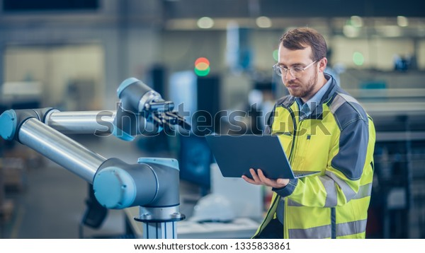 At the Factory: Automation Engineer Uses Laptop for Programming Robotic Arm. New Era in Automatic Manufacturing Industry.