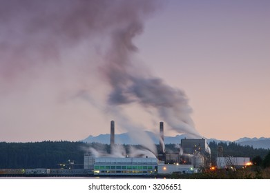 Factory belching out smog from its smokestacks lit by the evening light