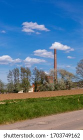 Factory chimney outside the city. Agriculture and industry Sunny weather in the countryside. A red brick chimney. Blue sky and clouds.