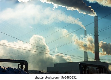 Factory chimneys smoke in the background of blue sky