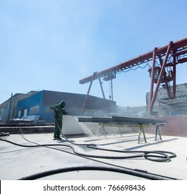 factory for cleaning of metal by sandblasting. the worker performing the cleaning by sandblasting of metal structures