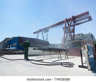 factory for cleaning of metal by sandblasting. a worker cleans the metal by sandblasting