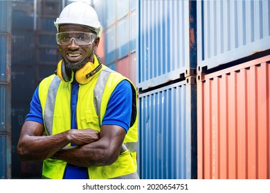 Factory engineer African worker man standing confidence with green working suite dress and safety helmet n front of container and cargo space. Business people working in shipping transport industry.