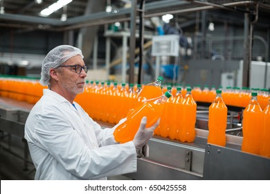 Factory engineer examining a bottle of juice in bottle factory