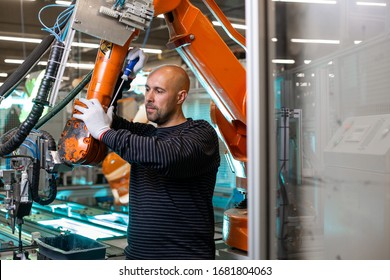 Factory engineer operating with automatic robot arms in automotive industry, modern automotive factory
