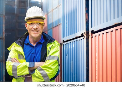 Factory engineer worker man standing confidence with green working suite dress and safety helmet n front of container and cargo space. Business people working in shipping transport industry.