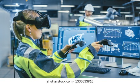 Factory: Female Industrial Engineer Wearing Virtual Reality Headset and Holding Controllers, She Uses VR technology for Industrial Design, Development and Prototyping in CAD Software.