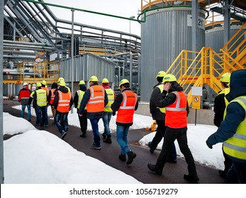 factory inspection. group of visitors on the factory tour. people go in helmets and uniforms for an industrial enterprise. 