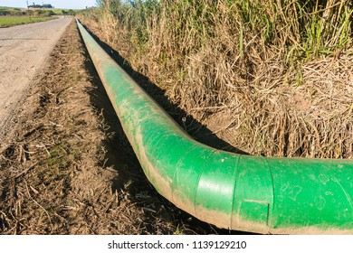 Factory long large green painted pipe transporting water from pump station alongside countryside dirt road landscape.