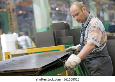 Factory Man Worker  Removing Metal Burrs from Steel Sheet with Deburring Tool at Workshop Machine Equipment