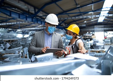 Factory manager with face protection mask visiting production line and discussing with worker about efficiency or production deadline. Industrial health measures during corona virus pandemic.