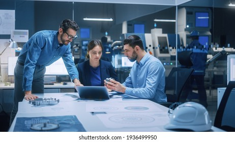 Factory Office Meeting Room: Team of Engineers Gather Around Conference Table, They Discuss Project Blueprints, Inspect Mechanism, Find Solutions, Use Laptop. Industrial Technology Factory
