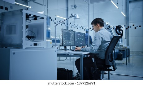 Factory Office: Portrait of Beautiful and Confident Male Industrial Engineer Working on Computer, on Screen Industrial Electronics Design Software. High Tech Facility with CNC Machinery