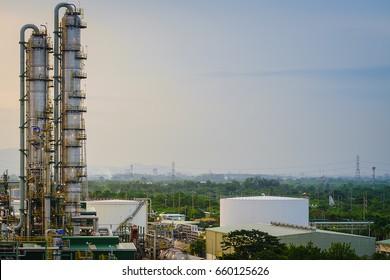 Factory on green park and sky background, Distillation tower in oil refinery plant, Column and storage tank in petrochemical plant